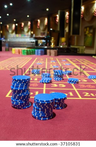 Game chesspieces on a table of roulette - stock photo