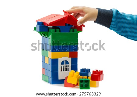 Game constructor and the hand of of the child isolated on white background.This is not a Lego, given manufacturer, different form and fixation, size - stock photo