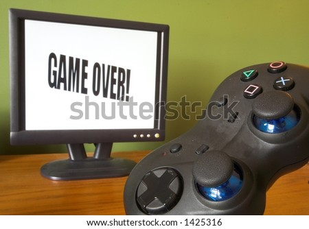 game controller and screen showing game over - stock photo
