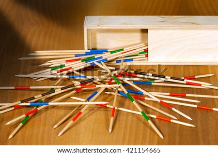 Game of mikado or shanghai with wooden sticks and box, on a brown table  - stock photo