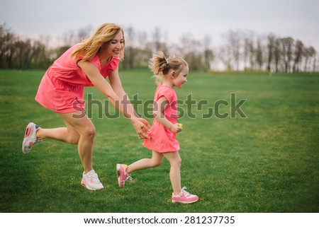 Game of tag. Happy young mother running after her daughter outdoors in park - stock photo
