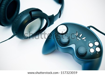 Gamepad and headphones on white background - stock photo