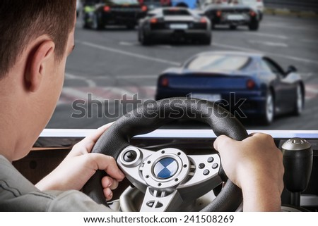 gamer driving autosimulator on the background screen with the game - stock photo