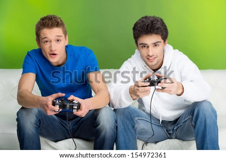 Gamers with joystick. Two young gamers playing video games while sitting on the couch - stock photo
