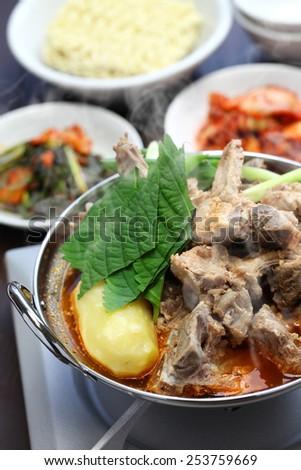 gamjatang, pork bone and potato soup, korean cuisine, simmering on the portable gas stove - stock photo