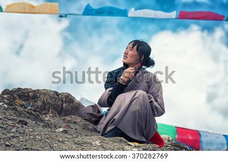 GANDEN, TIBET - APRIL 20: Tibetan woman rests during pilgrimage to the sacred Ganden monastery on 20 April, 2013 in Ganden, Tibet. Ganden monastery is one of the holiest religious sites in Tibet. - stock photo