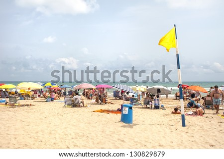 GANDIA,SPAIN-JULY 26: Unidentified people on the beach with yellow caution flag on July 26.2012 in Gandia, Spain. With caution the bathroom is not advisable, either by the sea state - stock photo