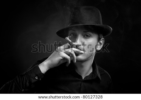 Gangster look. Handsome man with hat and cigar. - stock photo
