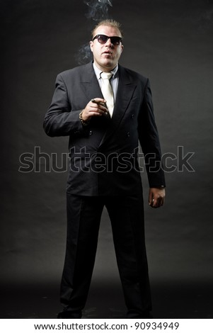 Gangster mafia man in suit with tie and sunglasses looking tough isolated on dark background - stock photo