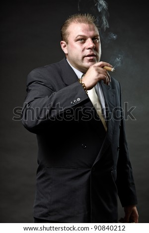 Gangster mafia man in suit with tie looking tough isolated on dark background - stock photo