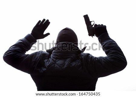 Gangster with a gun putting his hands up - stock photo