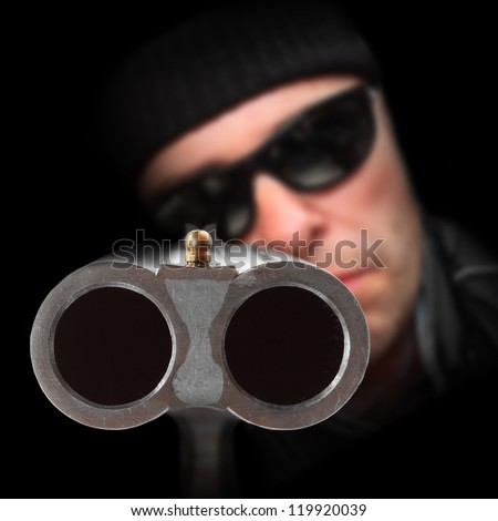 Gangster with shotgun aimed at you. Gun control concept. Close up with shallow DOF. - stock photo