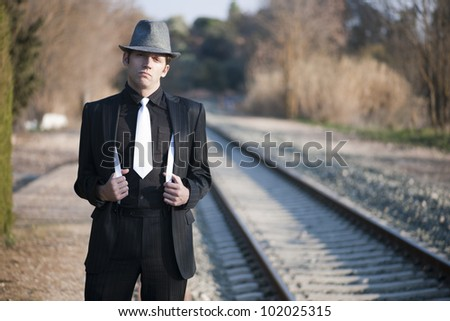 Gangster with straps and hat next to train tracks - stock photo