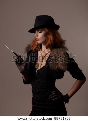 Gangster woman in fedora hat and evening dress holding mouthpiece