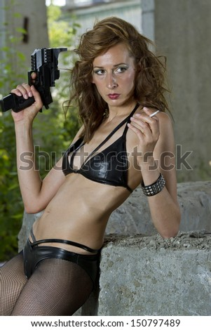 Gangster woman with a gun and cigarette in old fabric - stock photo