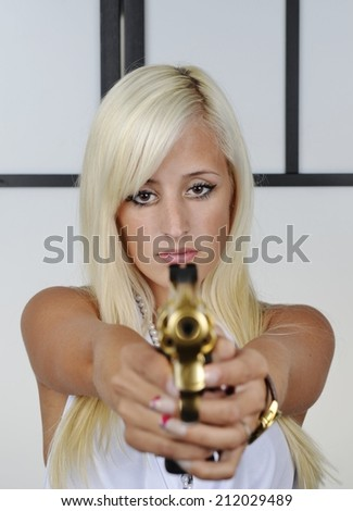Gangster woman with pistol isolate to the background. Sensual female blonde bandit points snub nose revolver handgun weapon, with focus on girl. - stock photo