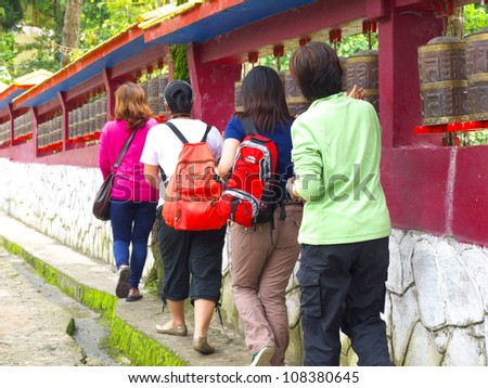 GANGTOK, SIKKIM/ INDIA-JUNE 12: Tourists turning the prayer wheels and praying at Enchey Monastery on June 12, 2012 in Gangtok. This can make Buddhists stay in concentration and get the merit. - stock photo