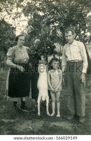 GANSERNDORF, AUSTRIA, CIRCA 1930s: vintage photo of farmers family with a goat outdoor , Ganserndorf, Austria , circa 1930s