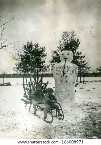GANSERNDORF, AUSTRIA, CIRCA 1930s - Vintage photo of two brothers on sled and snowman,  Ganserndorf, Austria, circa 1930s