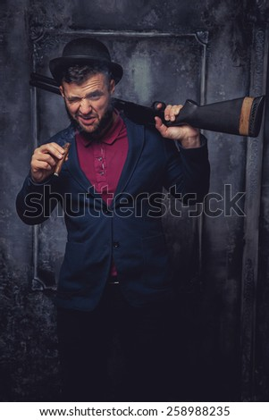 Ganster smoking a cig.Against art-wall on the background - stock photo