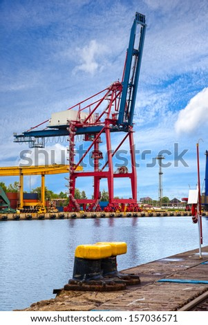Gantry cranes in a harbor on a background of the blue sky. - stock photo