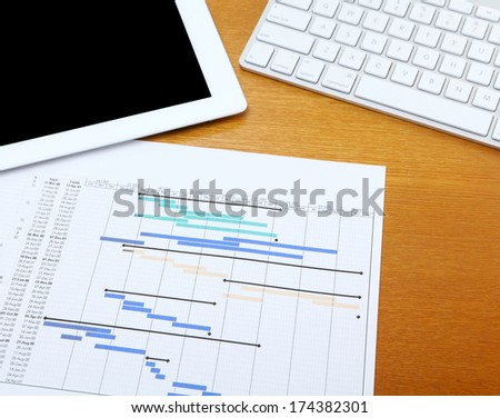 Gantt chart with tablet and computer keyboard - stock photo