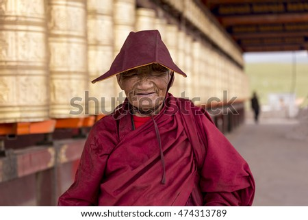 GANZI TIBETAN SICHUAN CHINA -AUGUST-19-2016 :Old woman poses smiling with camera in Yarchen Gar ( The Giant Monasteries of Kham). a famous Lamasery in Baiyu, Sichuan, China