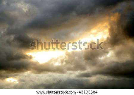 Gap in dark ominous clouds. Dramatic sky. - stock photo