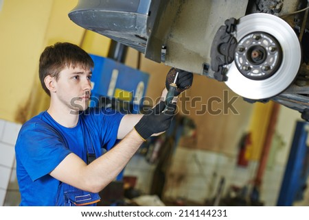 garage auto mechanic repairman checking car brake during automobile maintenance at repair service station - stock photo