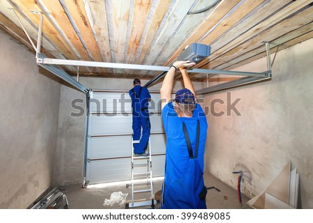 Garage doors installation.Workers installing lifting system  - stock photo