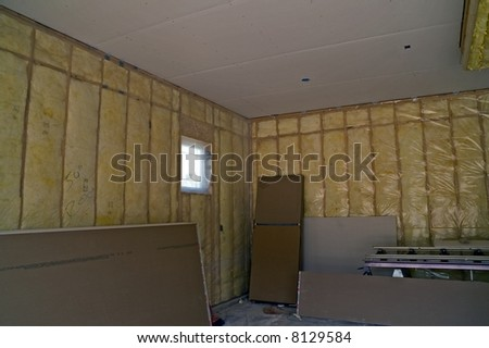 Garage for new single-family home with insulation covered with plastic - stock photo