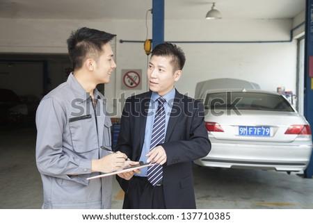 Garage Mechanic Explaining to Customer - stock photo