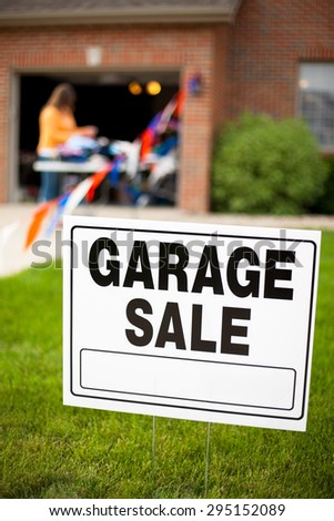 Garage sale sign on the front yard of a suburban home with a woman looking at items on a table. - stock photo