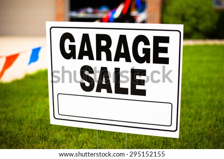 Garage sale sign on the front yard of a suburban house - stock photo