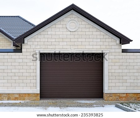 Garage with modern gate. Design of the facade of the estate. - stock photo
