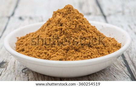 Garam masala or mix spices blend in white bowl over wooden background - stock photo