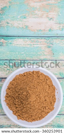 Garam masala or mix spices in white bowl over wooden background - stock photo