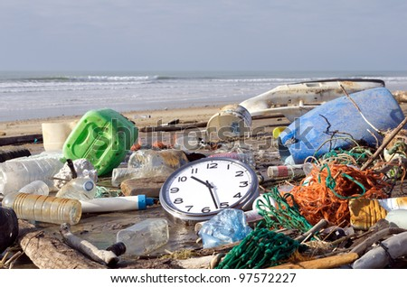 Garbage and waste washed up on a beach. It's time to wake up! - stock photo