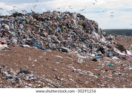 Garbage at a rubbish dump in a landfill site with a green,residential backdrop