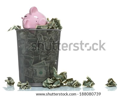 Garbage can full of money spilling over with piggy bank in it copy space - stock photo