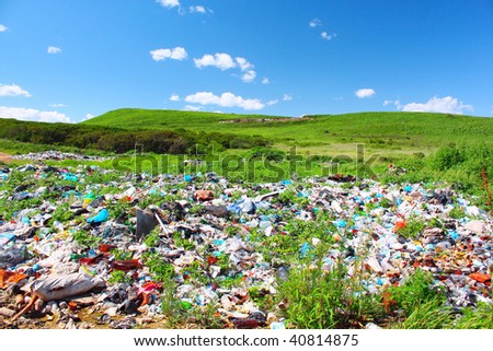 Garbage dump on green meadow - stock photo