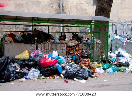 Garbage dumpsters cardboard boxes and bags full of trash - stock photo