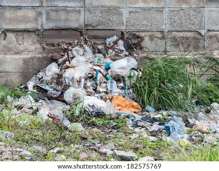 garbage heap beside the old wall in urban station. - stock photo