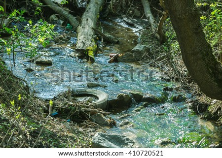 Garbage in spring steam. Tainted water resources, water pollution idea - stock photo