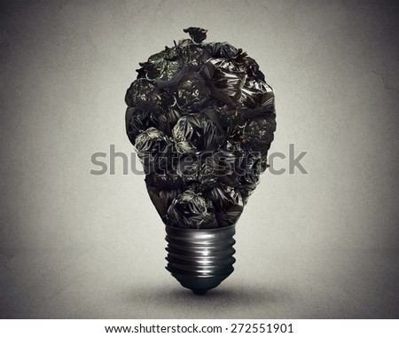 Garbage management solutions concept group of black trash bags shaped as light bulb as a symbol and icon of environmental damage and recycling waste issues isolated on grey background  - stock photo