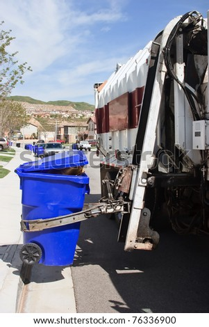 Garbage truck makes a stop to pick the trash bin. - stock photo