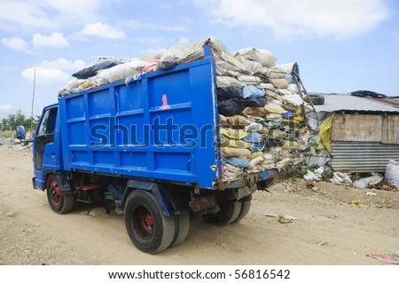 Garbage truck overflowing with trash in old sacks - stock photo