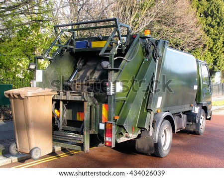 Garbage truck with a bin at the rear - stock photo