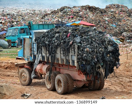 Garbage Trucks work on the landfill - stock photo