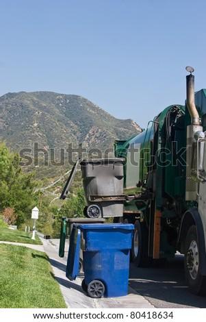 Garbage vehicle picks up a trash bin. - stock photo